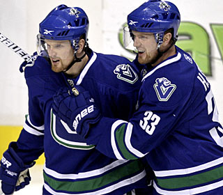 Daniel Sedin celebrates one of his three goals with twin brother, Henrik (33). (AP)