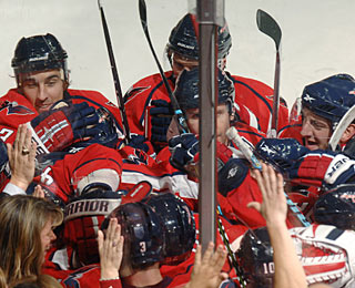 Fans celebrate along with Capitals players who overwhelm Mike Green after his winning goal. (AP)