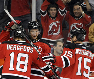 Travis Zajac and Jamie Langenbrunner congratulate Niclas Bergfors who gets two goals in the first. (AP)