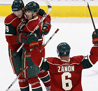 Mikko Koivu (9), who sets up both Wild goals, embraces Marek Zidlicky, who nets the winner. (AP)