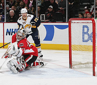 Brian Elliott makes a glove save as Jason Pominville hopes for a rebound. (Getty Images)