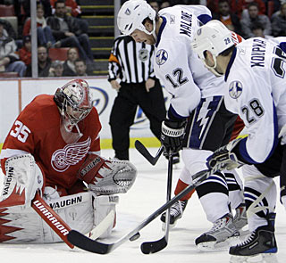 Jimmy Howard blocks Ryan Malone's shot as Zenon Konopka hunts for the rebound. (AP)