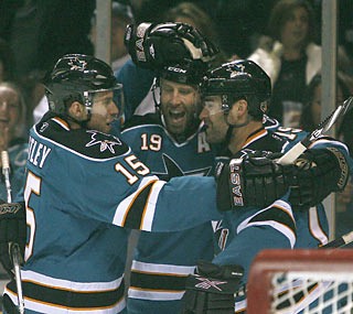 Patrick Marleau (right) celebrates with teammates moments after reaching the 300-goal milestone. (AP)