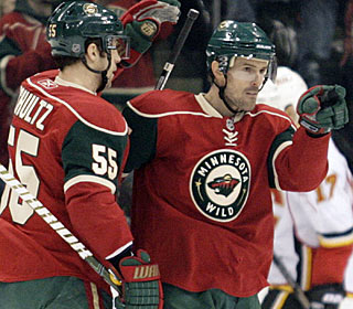Eric Belanger (right) makes the best of his 600th NHL game by scoring twice for the Wild. (AP)