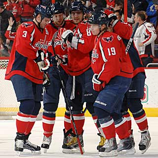Capitals surround Alex Ovechkin after he tallies his first goal as the team's captain. (Getty Images)
