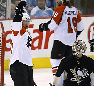 Jeff Carter, who scores twice versus the Penguins again, enjoys it while Brent Johnson looks on. (AP)