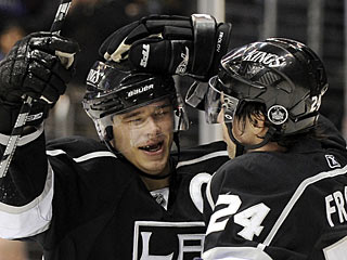 Dustin Brown celebrates his 100th career goal after a nice give-and-go with Alexander Frolov. (AP)