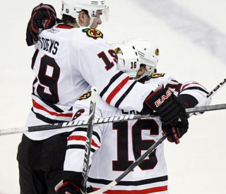 The Blackhawks mob Patrick Sharp after the game winner.  (AP)