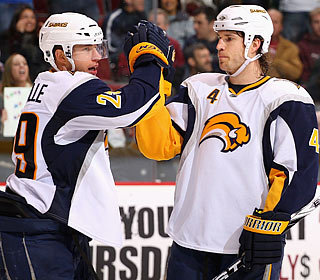 Jason Pominville (left) receives props from Steve Montador for a third-period goal.  (Getty Images)