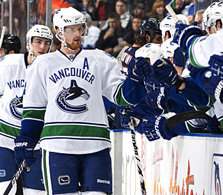 Henrik Sedin (center) sets up Daniel in overtime as the brothers also get assists on the first two goals. (AP)