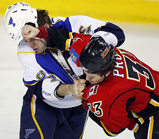 St Louis' Cam Janssen loses his helmet as he battles with Calgary's Brandon Prust.  (AP)