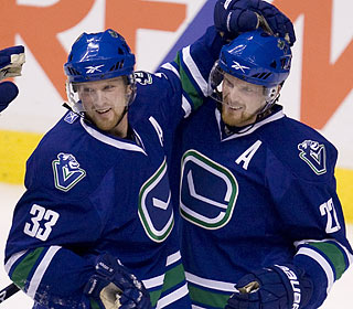 Henrik Sedin celebrates his second-period goal with brother Daniel as the Canucks win a fifth in a row.  (AP)