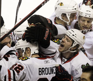 Troy Brouwer (22) is mobbed by his teammates after scoring the winner 97 seconds into overtime. (AP)
