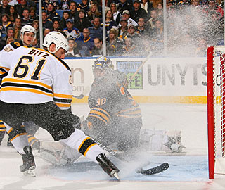 Ryan Miller makes an effort through the snow shower to stop Byron Bitz from scoring. (Getty Images)