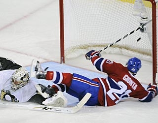 Brian Gionta goes down, but manages to backhand the puck into the net for the first of his two goals. (AP)