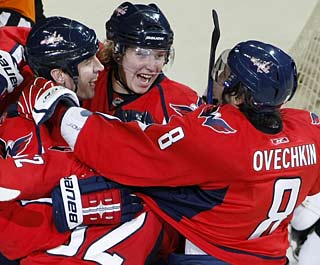 Mike Knuble (left) celebrates with Nicklas Backstrom and Alex Ovechkin.  (AP)