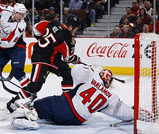Chris Neil skates around goalie Semyon Varlamov and flips a backhander in the net. (Getty Images)