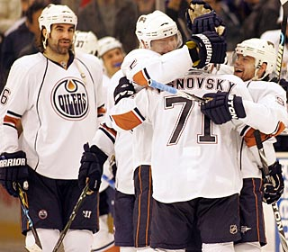Oilers congratulate Lubomir Visnovsky (71), whose 10th-round shootout goal is the winner.  (AP)