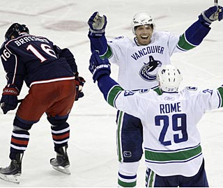 Mikael Samuelsson scores the third straight goal for Vancouver to complete a rally. (AP)