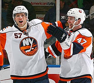 Andrew MacDonald is among the first to congratulate Blake Comeau (57) on his hat trick.  (Getty Images)