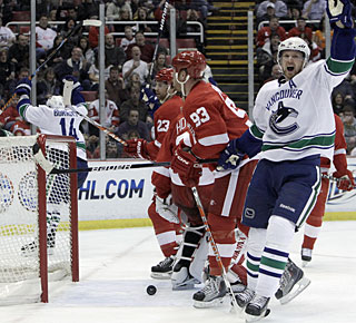 Henrik Sedin, who gets an assist, celebrates Alexandre Burrows' goal in the first period. (AP)