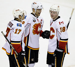 Teammates gather around Jarome Iginla (12) after he earns a hat trick to end his 10-game goal drought.  (AP)
