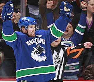 Henrik Sedin celebrates scoring a goal that's assisted by his identical brother Daniel. (Getty Images)