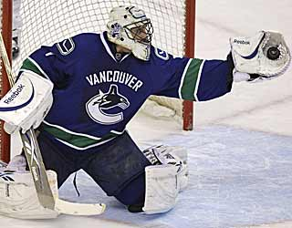 The Canucks' Roberto Luongo uses his glove to snag one of his 32 saves against the Sharks. (AP)