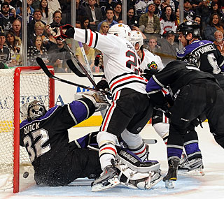Kings' Jonathan Quick gets pushed into the net as Troy Brouwer (22) scores the first goal. (Getty Images)