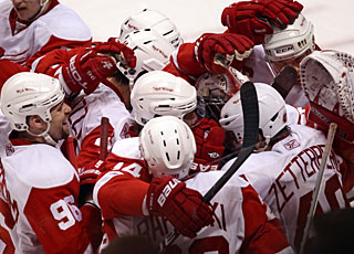 Henrik Zetterberg (40) is mauled by his teammates after netting a backhander with one tick to go. (AP)