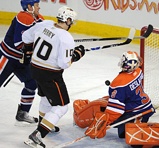 Corey Perry deflects the puck in front of goalie Jeff Deslauriers for the first of his two goals. (AP)