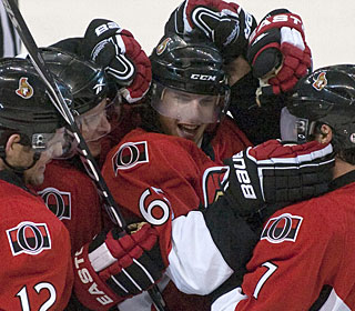 Erik Karlsson is overwhelmed by teammates after sending the game to OT with 7.7 seconds left. (AP)