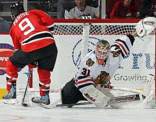 Antti Niemi makes a pad save on Zach Parise in the shootout to preserve a 'Hawks win. (Getty Images)