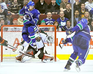 Daniel Sedin jumps to avoid Sami Salo's slap shot in OT, which eludes Niklas Backstrom.  (Getty Images)