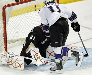 Los Angeles' Anze Kopitar sweeps the puck around Curtis McElhinney for the winning shootout goal.  (AP)