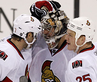 Goalie Brian Elliott gets happy cheers from Matt Cullen (left) and Chris Neil. (AP)