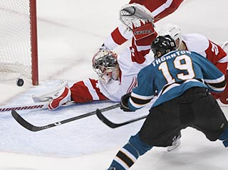 Jimmy Howard lunges but can't stop Joe Thornton's shot from going in the net and deciding the game. (AP)